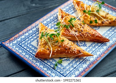 Traditional Turkish meat patty - burek served on a blue plate against a dark background. B?rek made of a thin flaky dough such as phyllo or yufka, typically filled with meat. - Shutterstock ID 1992271361