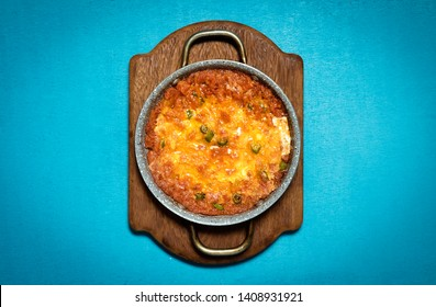 Traditional Turkish menemen which includes eggs, tomato, green peppers, and spices such as ground black and red pepper cooked in olive oil or sunflower oil