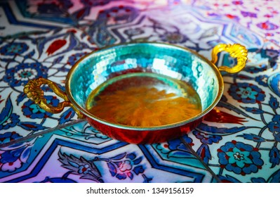 Traditional Turkish metal bowl for Menemen scrambled egg, tile with oriental floral ornament on the background.