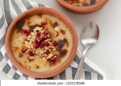 Traditional Turkish oven rice pudding and on white backround.There are walnuts and pomegranate on the rice puding.Top view.