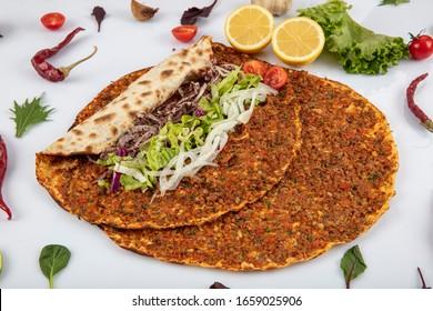 Traditionelle türkische Pizza, Lahmacun genannt, die mit Fleisch, Zwiebeln und Petersilie zubereitet wird, wird ausgestellt. Türkisches Lahmacun unter grünem Gemüse auf weißem Hintergrund. Lahmacun Restaurant Konzept.