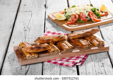 Traditional Turkish Ramadan baked dish pide. Turkish pizza pide, tomatoes, wooden spoon on the table. Middle eastern appetizers. Turkish cuisine. Bafra Pidesi is a stye of bread from blacksea area.