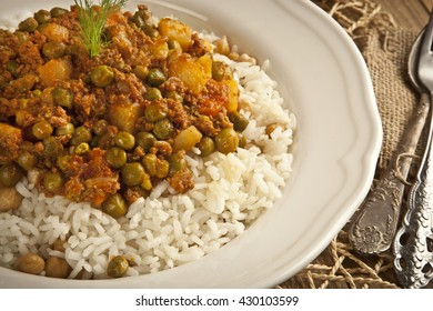 Traditional Turkish Rice pilaf with meat and vegetables pea in white plate on wooden concept background