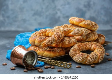 Traditional Turkish Simit Bagels with sesame seeds and scattered coffee beans on a dark textured background, selective focus.