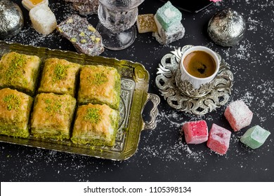 Traditional Turkish six slices of pistachio baklava,on the silver tray near Turkish coffee and Turkish Delight.Top view,isolated on black surface.Sugar Feast (Bayram)after Ramadan Eve.
