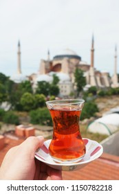 Traditional Turkish tea in a glass on a plate in the hands of a man with a mosque Ayasofya background. Travel to Turkey. Soft focus and beautiful bokeh.