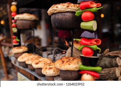 Traditional turkish testi kebap in a ceramic pots under dough baking on fire in brazier (grill) in Goreme, Cappadocia. Vegatables (tomato, aubergine, pepper, onion, zucchini) are going to be grilled.