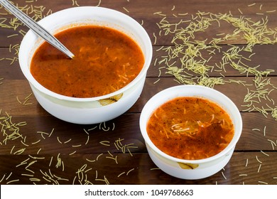 Traditional Turkish vermicelli soup, cooked with tomato sauce, mince and onion, in porcelain bowls on wooden table with vermicelli grains