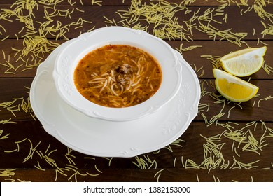 Traditional Turkish vermicelli soup,in the stylish soup set on the wooden table with slices of lemon.