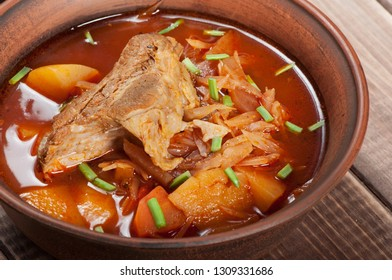 Traditional Ukrainian borsch with meat on the edge, in a brown clay bowl, on a wooden background.