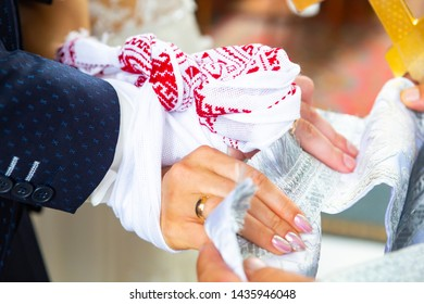 traditional Ukrainian Christian Wedding. the priest tied his hands to the newlyweds with a wedding towel on church.