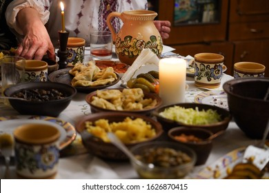 Traditional Ukrainian dinner. Orthodox Christmas Eve. Table with traditional Ukrainian homemade food and decorated pottery in front of a host old lady in traditional embroidered shirt.