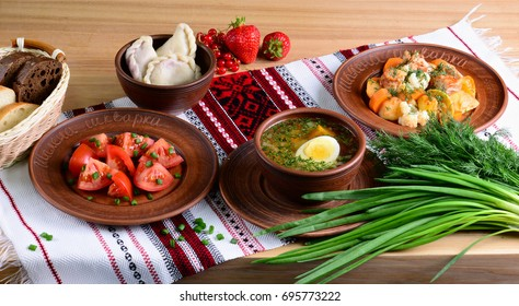 Traditional Ukrainian dinner: vegetable soup with boiled egg, salad with tomatoes in sunflower oil, vareniki with berries, vegetable stew on tablecloths with ornament.
