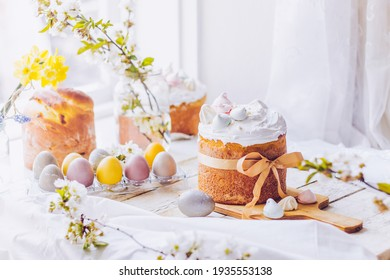 Traditional ukrainian easter cake with white swiss meringue. New cruffin cake trend 2021. Spring cherry blossom and colorful painted eggs. Person decorates cake with hand. Free copy space. - Shutterstock ID 1935553138