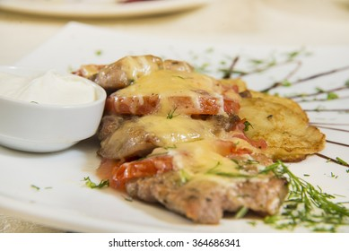 Traditional ukrainian potato pancakes with fried tomatoes and sour sauce