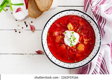 Traditional Ukrainian Russian borscht with white beans on the bowl. Beetroot soup. Plate of red beet root soup borsch on white table. Traditional Ukraine food cuisine. Top view