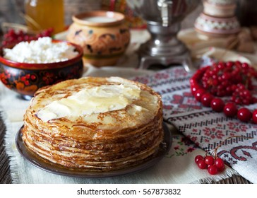 Traditional Ukrainian or Russian pancakes with cottage cheese and sour cream on napkins with embroidery. Traditional dishes on the holiday Carnival Maslenitsa Shrovetide.