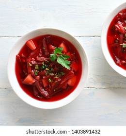 Traditional ukrainian russian soup (borscht) with greens. Beetroot soup in bowl on white wooden background. Top view, flat lay