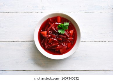 Traditional ukrainian russian soup (borscht). Beetroot soup in bowl on white wooden background with copy space. Top view, flat lay