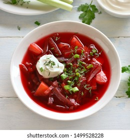 Traditional ukrainian russian soup (borscht) with greens and sour cream. Beetroot soup in bowl on white wooden background. Top view, flat lay