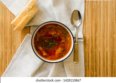 Traditional Ukrainian Russian vegetable soup borsch. Two pieces of bread. Serving method with a textile napkin. A cup of borsch is decorated with greens. Design in a rustic style.