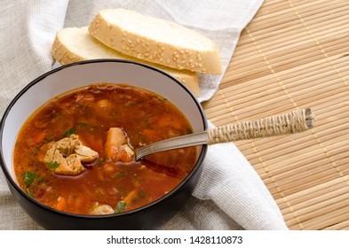 Traditional Ukrainian Russian vegetable soup borsch. Two pieces of bread. Serving method with a textile napkin. A cup of borsch is decorated with greens. Design in a rustic style. Close-up