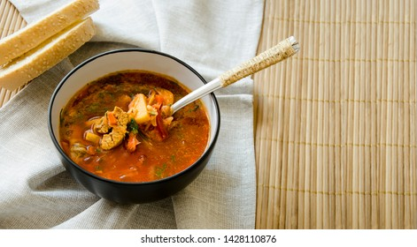 Traditional Ukrainian Russian vegetable soup borsch. Two pieces of bread. Serving method with a textile napkin. A cup of borsch is decorated with greens. Design in a rustic style. Banner, copy space.