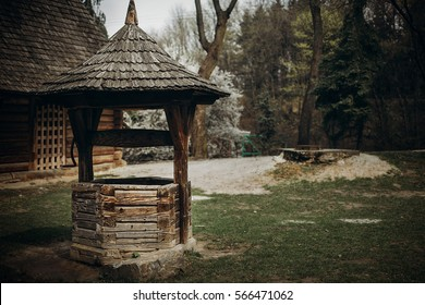 Traditional ukrainian water well, rustic old wooden well in a farm yard in countryside village, ethnic architecture building close-up, agriculture concept