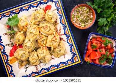 Traditional uzbek manti steamed with minceed meat and tomato paprika salad as top view on a plate