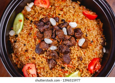 Traditional uzbek pilaf with meat, vegetables and garlic. Top view. Close up