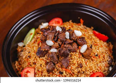 Traditional uzbek pilaf with meat, vegetables and garlic. Close up