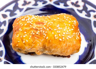 Traditional uzbek samsa bun with minced veal. Served on authentic oriental plate. Macro. Photo can be used as a whole background.