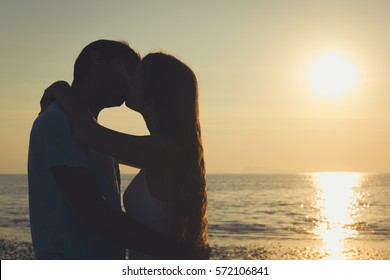 Traditional Valentines Day romantic scene of young couple in love kissing at sunset by the sea in the island of Koh Phangan, Thailand. Honeymoon, travel destination concept. Vintage effect