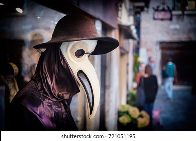 Traditional venetian mannequin in Plague doctor costume, mask and hat near shop window in the street of Venice, Italy. Toned image.