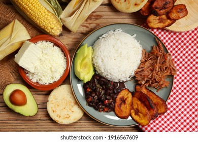Traditional Venezuelan dish of Rice, Shredded Beef, Black Beans, Avocado and fried Plantain known locally as Pabellon Criollo on a rustic wooden table
