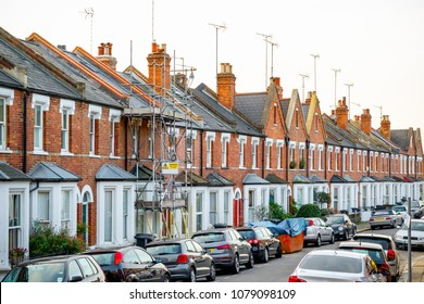 Traditional Victorian terraced houses, one covered with scaffolding, around West Hampstead in London