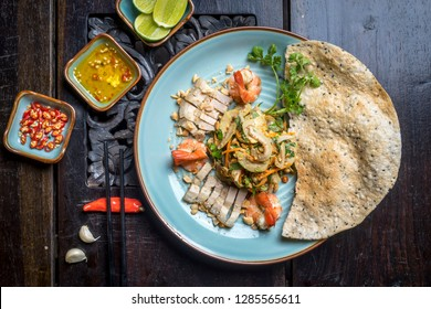 traditional VIETNAM food in Hue style (middle place in Vietnam) Rice with seafood (sausage, clam, squid, tiger prawn) in hot claypot. Decoration on very old wood table with lime, chili, garlic