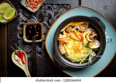 Traditional VIETNAM food in Hue style (middle place in Vietnam) Rice with seafood (sausage, clam, squid, tiger prawn) in hot claypot. Decoration on very old wood table with lime, chili, garlic,