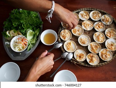 traditional VIETNAM food in mini dish rice pancake with local spice dried shrimp top served in bamboo basket tray with mild clear source and fresh green clean vegetable as appetizer or main couse dish