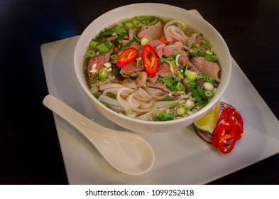 Traditional Vietnamese beef soup pho on a dark wooden table background. Pho Bo main dish. Close up.