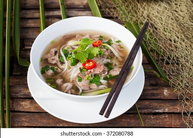 Traditional Vietnamese beef soup pho on a wooden background Copy space