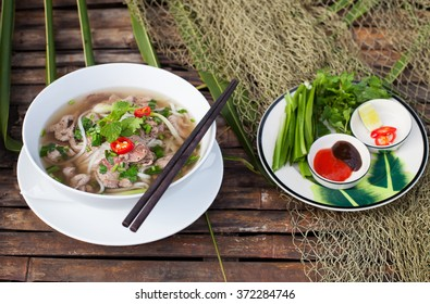 Traditional Vietnamese beef soup pho with sous Hoisin on a wooden background Copy space