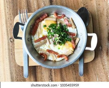 Traditional Vietnamese breakfast, pan of egg, chopped pork and Vietnamese sausage on wooden table, top view