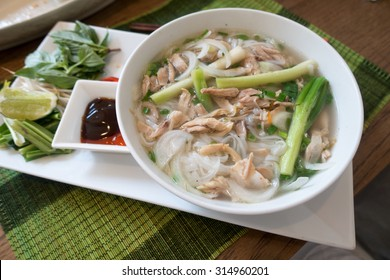 Traditional Vietnamese chicken soup pho on a wooden background.