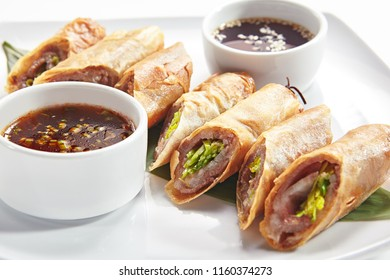 Traditional Vietnamese Deep Fried Spring Rolls, Eggroll or Lumpia with Duck Closeup. Crispy Sliced Springroll with Meat, Vegetables and Hot Sauces on a Banana Leaf Isolated on White Background