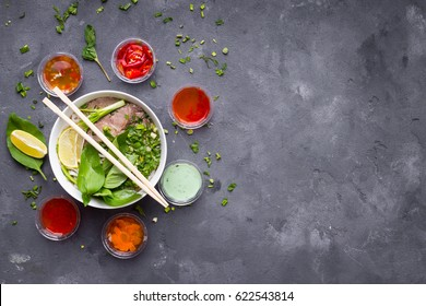 Traditional vietnamese noodle soup pho in bowl with assorted sauces on concrete background, space for text