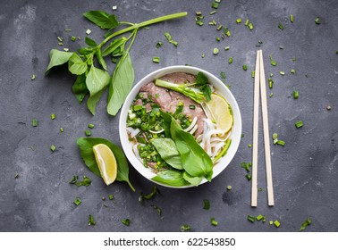 Traditional vietnamese noodle soup pho in bowl, garnished with basil, mint, lime, on concrete background