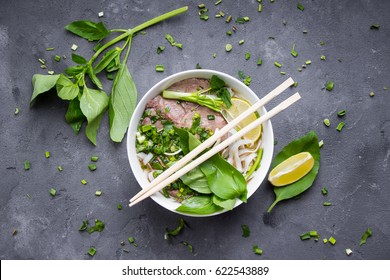 Traditional vietnamese noodle soup pho in bowl, garnished with basil, mint, lime, on concrete background. Vietnamese beef soup pho bo. Close-up. Asian/vietnamese food. Vietnamese dinner. Pho bo meal