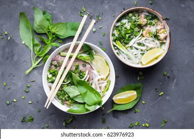 Traditional vietnamese noodle soups pho in bowls, concrete background. Vietnamese beef soup pho bo, chicken pho ga. Close-up. Asian/vietnamese food. Vietnamese dinner. Pho bo meal. Top view. Healthy