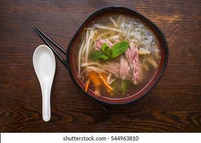 Traditional Vietnamese pho beef noodle soup garnished with mint leaves